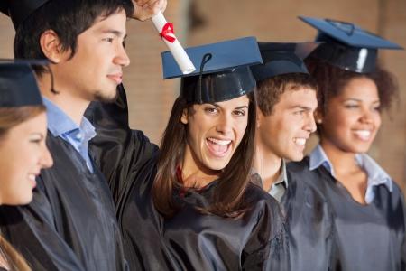 graduacion de universidad: Retrato del estudiante femenino emocionada la celebración de certificado mientras está de pie con sus amigos en la universidad
