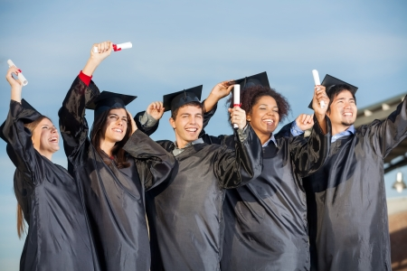 Excited male and female students holding certificates against sky photo