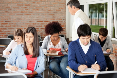 Group of multiethnic students writing exam while teacher supervising them in classroom Stock Photo - 23800865