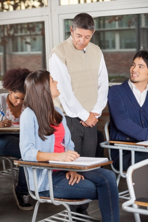 Young students looking at teacher while giving exam in classroom photo
