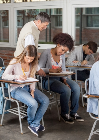 Young university students writing exam while professor supervising them in classroom photo