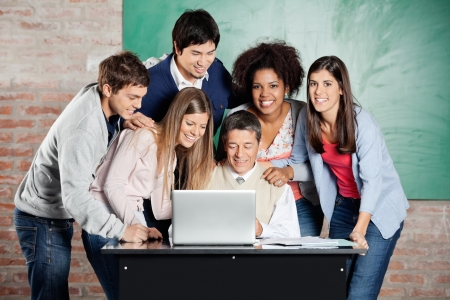 Portrait of female students standing with classmates while teacher teaching on laptop in classroom photo