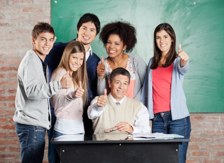 Portrait of happy multiethnic students and professor gesturing thumbsup at desk in classroom photo