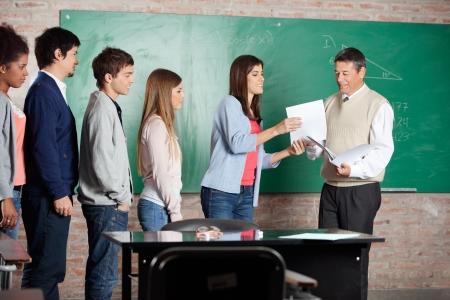 同級生の教室で列に並んで立っている間学生にテスト結果を与えて成熟した男性教師 写真素材 - 23800889