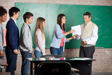 Mature male teacher giving test result to student while classmates standing in row at classroom Stock Photo - 23800889