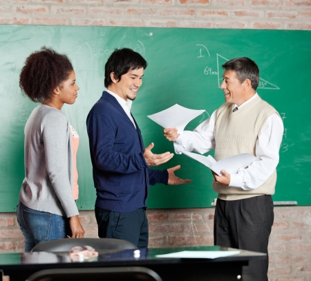 Happy mature professor giving test result to male student with classmates standing in a row at classroom Stock Photo - 23726130