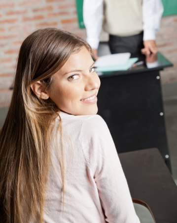 Rear view portrait of beautiful college student sitting at desk in classroom photo