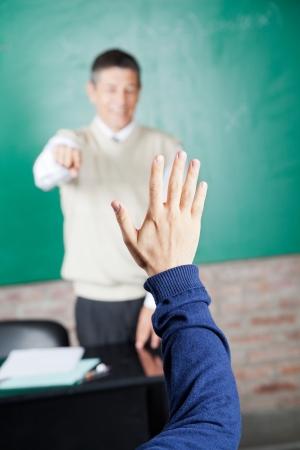 Image recadrée de la main d'étudiant avec le professeur pointant sur lui en classe Banque d'images - 23802412