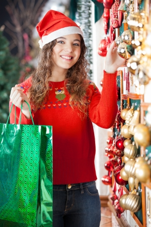 Portrait of beautiful woman in Santa hat with shopping bag buying Christmas ornaments at store photo
