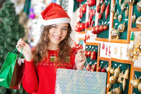 Portrait of happy young woman in Santa hat carrying shopping bags at store photo