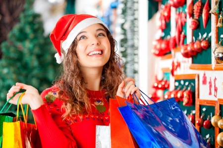 Happy woman in Santa hat looking up while carrying shopping bags at store photo