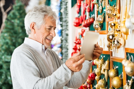 Happy senior man photographing Christmas ornaments through digital tablet at store photo
