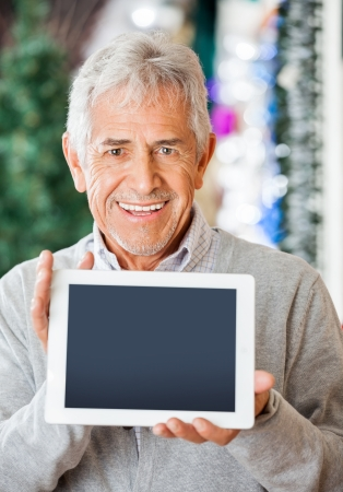 Portrait of happy senior man displaying digital tablet at Christmas store photo