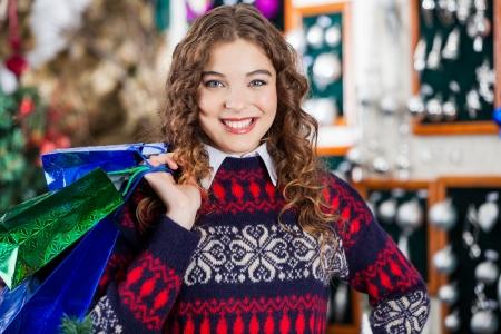 bureta: Retrato de mujer joven feliz con bolsas de compras en la tienda de Navidad