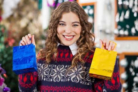 bureta: Retrato de mujer joven feliz celebraci�n de las peque�as bolsas de la compra en la tienda de Navidad