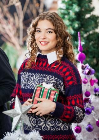 bureta: Retrato de mujer joven y bella celebración de Navidad en la tienda Foto de archivo