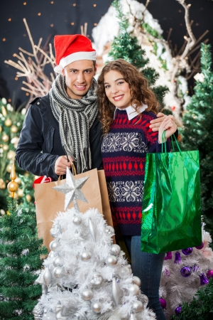 Portrait of happy young couple with shopping bags standing at Christmas store photo
