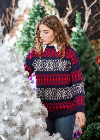 Young woman buying decorated Christmas tree in store photo