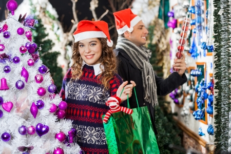 Portrait of happy young woman carrying shopping bag with man looking at decorations in store photo