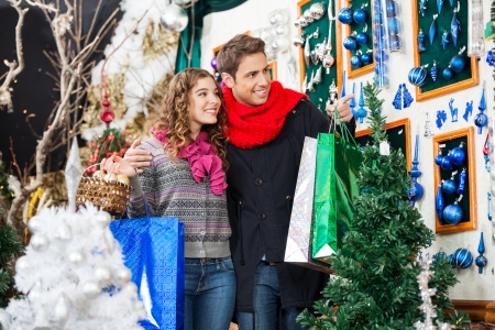 shoppingbag: Happy young couple with bags shopping at Christmas store