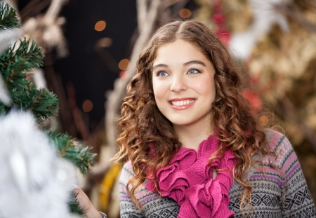 burette: Beautiful young woman smiling while looking away in Christmas store