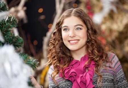 bureta: Joven y bella mujer sonriendo mientras mira lejos en la tienda de Navidad