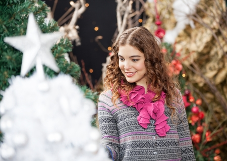 burette: Beautiful young woman smiling while shopping at Christmas store Stock Photo