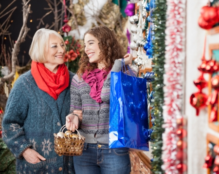 Happy mother and daughter with bags shopping in Christmas store photo