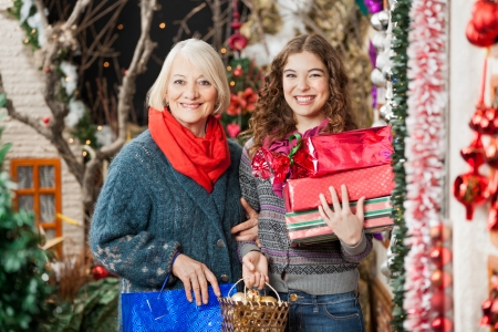 Portrait of happy mother and daughter with Christmas presents standing together at store photo