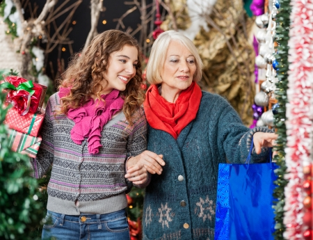 Happy mother and daughter shopping for Christmas ornaments in store photo