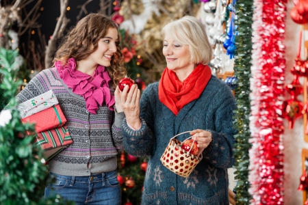 Happy mother and daughter with bauble basket and presents standing in Christmas store photo
