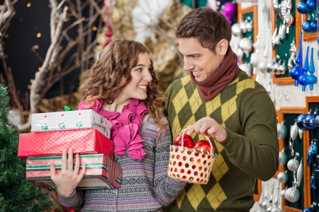 Happy young couple with Christmas presents and bauble basket in store photo
