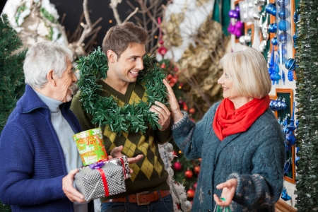 Happy parents looking at son with wreath around neck at Christmas store photo