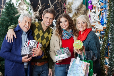 Portrait of happy family with Christmas presents and shopping bags standing together in store photo