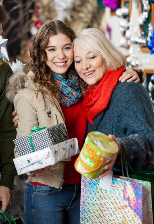 Affectionate mother and daughter with Christmas presents standing at store photo