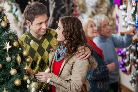 Happy young couple in Christmas store with parents shopping in background photo