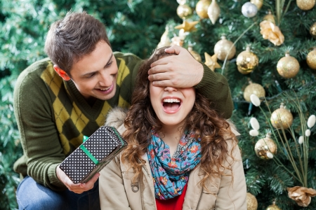 woman mouth open: Young man covering womans eyes while surprising her with gift in Christmas store