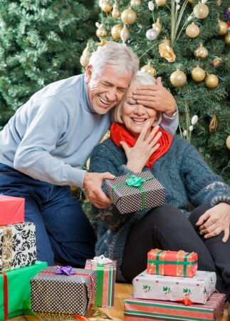 Happy senior man covering woman's eyes while surprising her with Christmas gifts in store photo