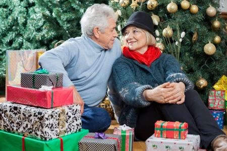 Senior couple looking at each other while sitting with presents on floor in Christmas store photo