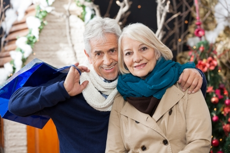 Portrait of happy senior couple with shopping bags standing at Christmas store photo