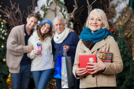 Portrait of happy senior woman holding Christmas presents with family standing in background at store photo