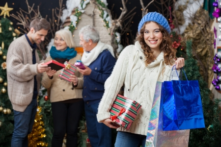 Portrait of beautiful young woman holding Christmas presents and shopping bags with family standing in background at store photo