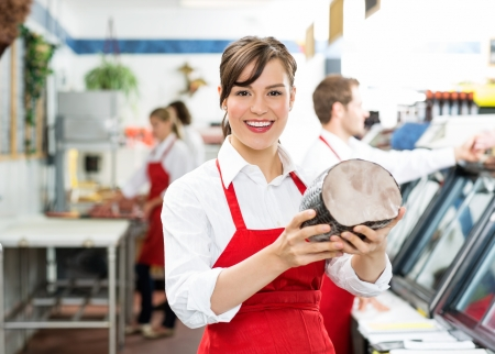 Portrait of happy female butcher holding ham at store with colleagues working in background photo