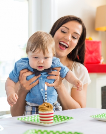 blow out: Mid adult mother with baby boy celebrating birthday with cupcake on table Stock Photo