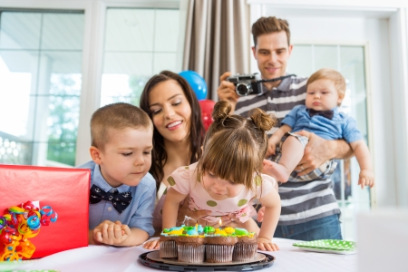 Family watching girl blowing out candles on birthday cake at home photo