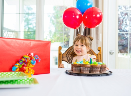 birthday decoration: Portrait of birthday girl with cake and present on table at home