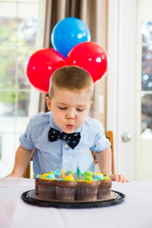 blow out: Birthday boy blowing candles on cake at home Stock Photo