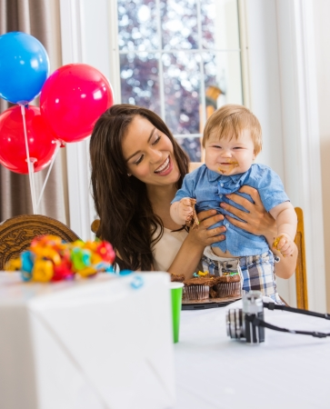 Happy mother holding baby boy with messy hands covered with cake icing at birthday party photo