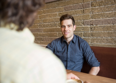 Portrait of handsome young man sitting at table in coffee shop photo