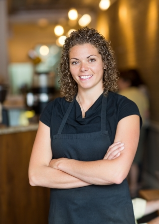 Portrait of beautiful mid adult waitress standing arms crossed in cafe photo